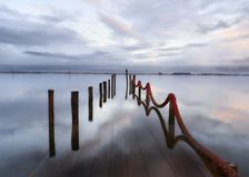 Palafitic pier submerged at sunset whit red rope stock images