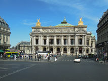 Palais Garnier, Paris. The golden statues of Palais Garnier, the famous opera house in Paris, glisten in the sunlight across a busy square Stock Photos