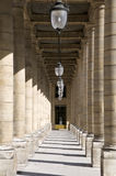 Palais Royal arcade. Neoclassical columns arcade in the Palais Royal of Paris on a sunny day Royalty Free Stock Photography