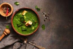 Palak paneer或菠菜和酸奶干酪咖喱,灰浆用在黑暗的背景的香料 传统印度盘 顶视图,拷贝 图库摄影