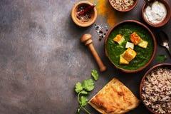 Palak paneer lub ser curry szpinak?w i cha?upy, mo?dzierz z pikantno??, naan, ry? na ciemnym tle karmowy indyjski tradycyjny obraz royalty free