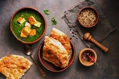 Palak-paneer oder Spinats- und Hüttenkäsecurry, Mörser mit den Gewürzen, naan, Reis auf einem dunklen Hintergrund Traditioneller  stockfoto