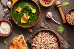 Palak paneer or Spinach and Cottage cheese curry,mortar with spices , naan, rice on a dark background. Traditional Indian food. Overhead view stock photo