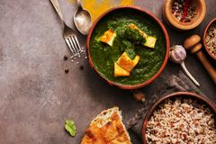 Palak paneer or Spinach and Cottage cheese curry,mortar with spices , naan, rice on a dark background. Traditional Indian food. Top view, copy space stock photos