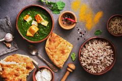 Palak paneer or Spinach and Cottage cheese curry, rice, spices , naan, on a dark background. Traditional Indian food. Overhead. View, copy space stock photography