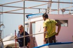 Palamos, Catalonia, may 2016: fisherman cleaning and repairing m Royalty Free Stock Photos