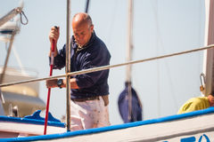 Palamos, Catalonia, may 2016: fisherman cleaning and repairing m Royalty Free Stock Images