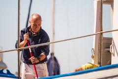 Palamos, Catalonia, may 2016: fisherman cleaning and repairing m Stock Photos