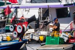 Palamos, Catalonia, may 2016: fisherman inspect and repairing fi Royalty Free Stock Photos