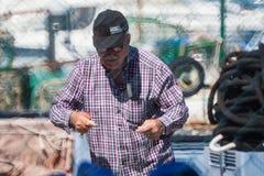 Palamos, Catalonia, may 2016: fisherman inspect and repairing fi Stock Photos