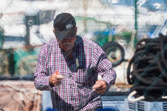 Palamos, Catalonia, may 2016: fisherman inspect and repairing fi Stock Photo