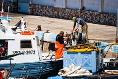 Palamos, Catalonia, may 2016: Fishermen cleaning and repairing m Royalty Free Stock Image