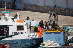 Palamos, Catalonia, may 2016: Fishermen cleaning and repairing m Stock Image