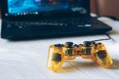 Palanca de mando transparente amarilla y un ordenador portátil con un videojuego en a Foto de archivo