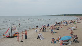 PALANGA, LITHUANIA - July 30, 2016: People relaxing, sunbathing and swimming at Palanga city Beach during hot summer day stock footage