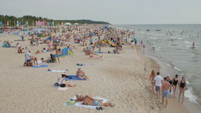 PALANGA, LITHUANIA - July 30, 2016: People relaxing, sunbathing and swimming at Palanga city Beach during hot summer day stock video footage