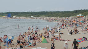 PALANGA, LITHUANIA - July 30, 2016: People relaxing, sunbathing and swimming at Palanga city Beach during hot summer day. PALANGA, LITHUANIA - June 28, 2016 stock footage