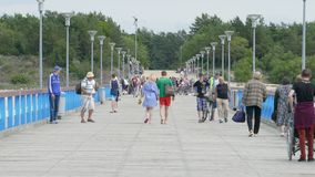Palanga Sea Bridge, Lithuania. PALANGA, LITHUANIA - June 28, 2016: Unidentified People walking on Palanga Sea Bridge during hot summer day stock video