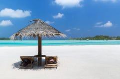 Palapa и sunbeds морским путем на пляже Мальдивов Стоковые Фото