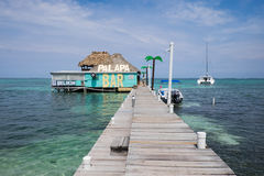 A palapa bar at the end of a dock in Belize. With a thatched roof and palm trees. There is a sailboat, blue sky with clouds, and blue and green ocean and sea Royalty Free Stock Photography
