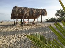 Palapa on a beach in Northwest Columbia on a sunny day. A large palapa with a thatched roof and hammocks on a quiet sandy beach with the ocean in the distance Royalty Free Stock Photo