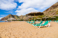 Palapa and chaise-longue on Playa de las Teresitas, Tenerife. Palapa and chaise-longue on golden sand of Playa de las Teresitas. San Andres village on background Royalty Free Stock Image