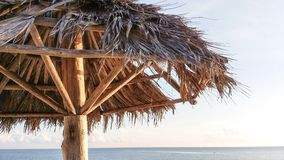 Palapa closeup with blue sky and ocean in background Royalty Free Stock Images