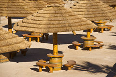 Palapa Huts. A cluster of palapa huts with palm frond roofs, sandy beach and wooden benches Royalty Free Stock Image
