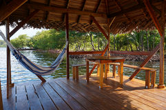 Palapa over water with hammock. Peaceful scene on a palapa over water with hammock and a table, Caribbean sea Royalty Free Stock Image