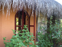 Palapa roof and picturesque window in an echo village Stock Photos