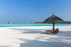 Palapa and sunbeds by sea on maldives beach. Travel, tourism, vacation and summer holidays concept - palapa and sunbeds over sea and sky on maldives beach Stock Image