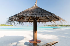 Palapa and sunbeds by sea on maldives beach. Travel, tourism, vacation and summer holidays concept - palapa and sunbeds over sea and sky on maldives beach Stock Images
