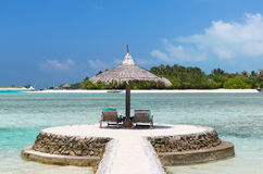 Palapa and sunbeds by sea on maldives beach. Travel, tourism, vacation and summer holidays concept - palapa and sunbeds over sea and sky on maldives beach Stock Photos