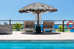 Palapa and sunbeds at seaside swimming pool. Travel, tourism, vacation and summer holidays concept - palapa and sunbeds at seaside swimming pool Royalty Free Stock Photo