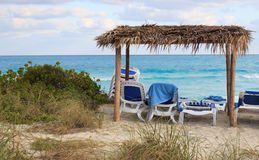 Palapas and lounge chairs overlooking the ocean n Royalty Free Stock Photo