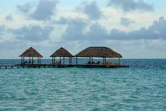 Palapas on an ocean pier Stock Images