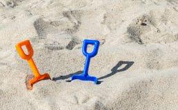 2 palas plásticas en una playa arenosa en un día de verano soleado Fotografía de archivo