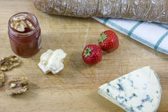 Palatable cheese roquefort and brie, bread, jam, nuts and strawberries as background Royalty Free Stock Photo