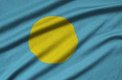 Palau flag is depicted on a sports cloth fabric with many folds. Sport team banner royalty free stock photo