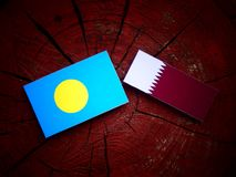 Palau flag with Qatari flag on a tree stump isolated. Palau flag with Qatari flag on a tree stump Stock Photos