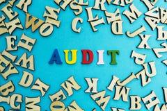 A palavra 'auditoria 'é apresentada das letras coloridos em um fundo azul imagens de stock royalty free