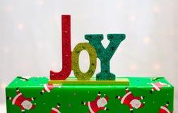 A palavra ALEGRIA em um presente de Natal Imagens de Stock