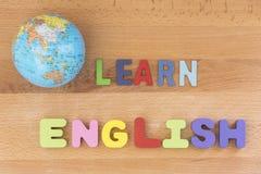 A palavra aprende o inglês com o globo sobre o fundo de madeira imagens de stock royalty free