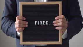 Palavra ateada fogo das letras na placa do texto no homem de negócios anônimo Hands filme