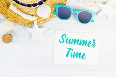Palavra azul das horas de verão no cartão branco na tabela de madeira com sunglasse Fotos de Stock