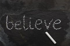 A palavra BELIEVE escrita com giz na pedra preta Fotografia de Stock Royalty Free