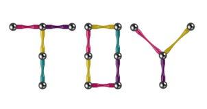 A palavra BRINQUEDO das varas e das bolas coloridas, elementos multicoloridos do construtor magnético rendição 3d ilustração stock