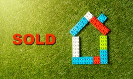 Palavra colorida Sold da casa de blocos do brinquedo escrita na grama conceito na indústria de estado real e de propriedade fotografia de stock royalty free