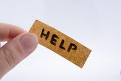 Palavra da ajuda em um papel da parte fotografia de stock