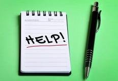 Palavra da ajuda no caderno Foto de Stock Royalty Free